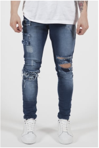 male model wearing blue skinny jeans, with ripped detailing on the pocket.