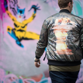 Male model wearing bomber jacket in front of a colourfully painted wall mural
