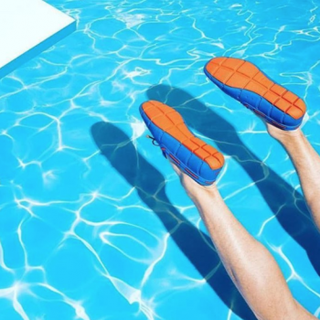 A pair of blue and orange swims shoes in a swimming pool