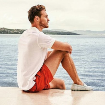 a man sat on a boat looking out onto the ocean, wearing Swims shoes