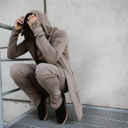 man crouched down holding his head, wearing a full beige tracksuit