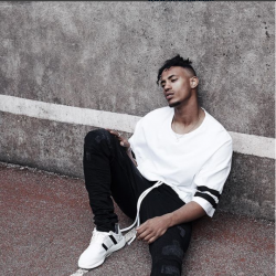 male model sat down looking at the camera, wearing white trainers and black jeans