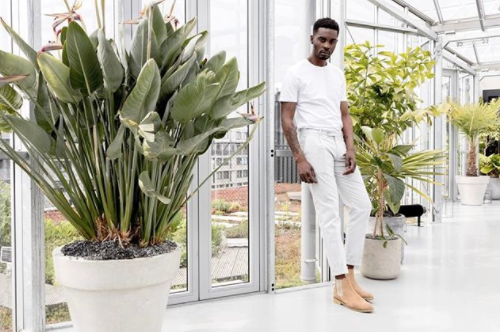 male model looking into the camera, wearing all white , and also wearing brown shoes.